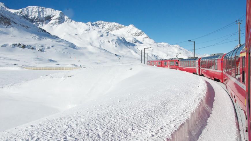 Paisaje de las montañas en invierno en medio de la nieve donde cruza el tren Rojo de Bernino en Suiza