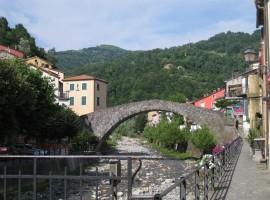 Vistas de las montañas llenas de vegetación,algunas casas y un puente en Varese Ligure, Liguria