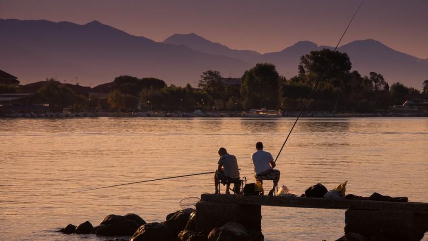 Atardecer en el río Mara, dos pescadores sentados en las rocas de la orilla, Liguria