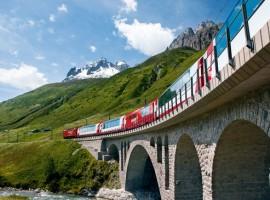 Recorrido del tren Glacier Express sobre un puente y al fondo la vegetación y las montañas