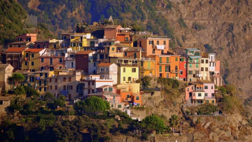 Paisaje de varias casas de colores puestas juntas una sobre la otra sobre la montaña, Liguria