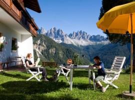 Disfrute de los turistas en el exterior del Residence Schopplhof – Funes Alto Adige, Italia
