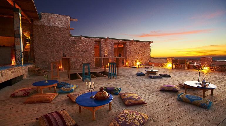 Ecohotel Ane Vert, en Marruecos. Espacio abierto con pequeñas mesas azules y almohadas arabes
