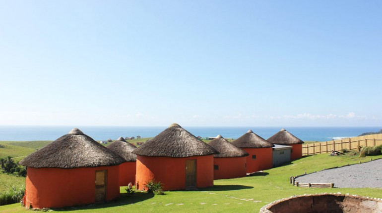 Casitas naranjas con techo de paja con increíble vista del mar, en África