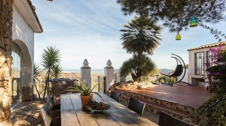 Casa Tarsan en España, inspirada por Gaudì. Mesa con sillas al exterior del edificio, con vista en el mar de Valencia